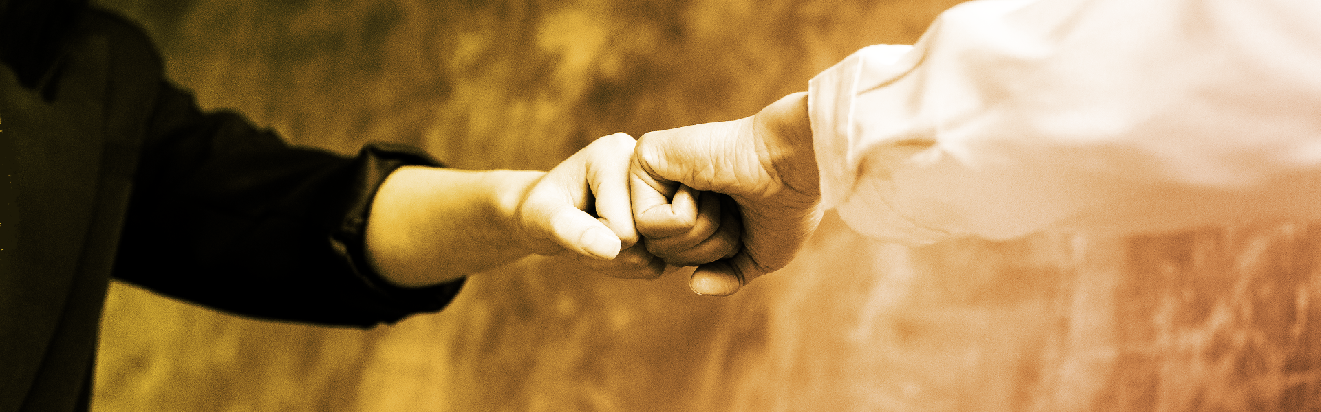 Stock image showing two peoples arms and fist bumping as a greeting