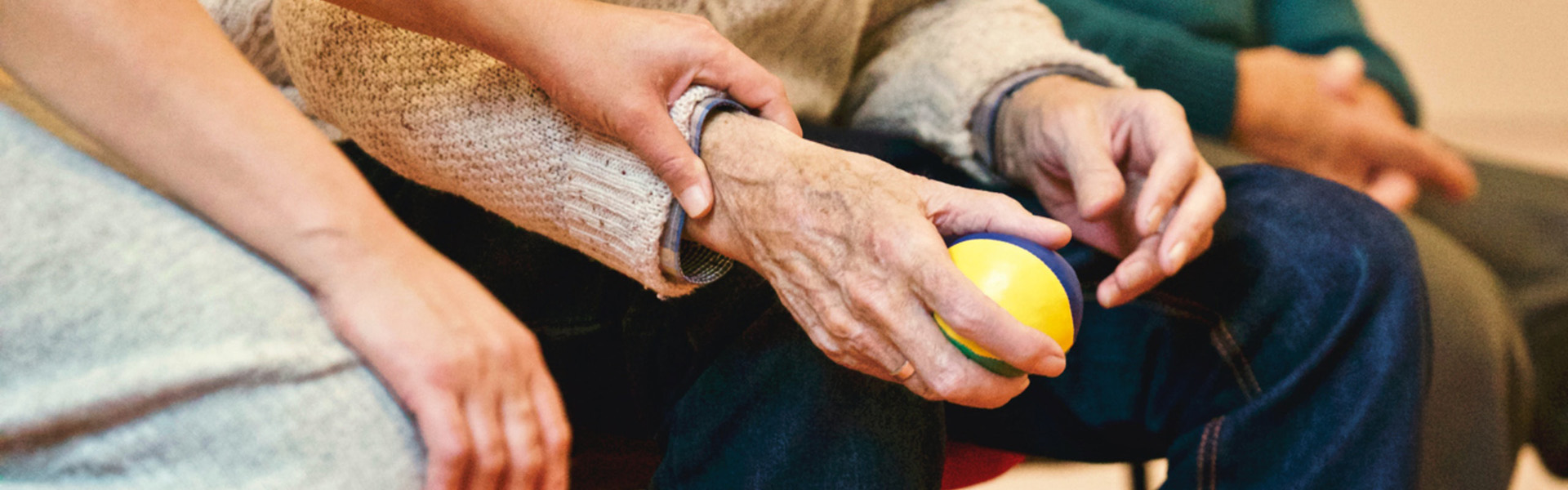 Stock photograph cropped to focus on the people sitting and their hands - one person is holding the elder's wrist as if supporting them.