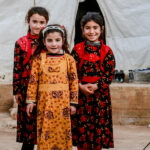 Stock photograph of 3 young Syrian children standing in a camp