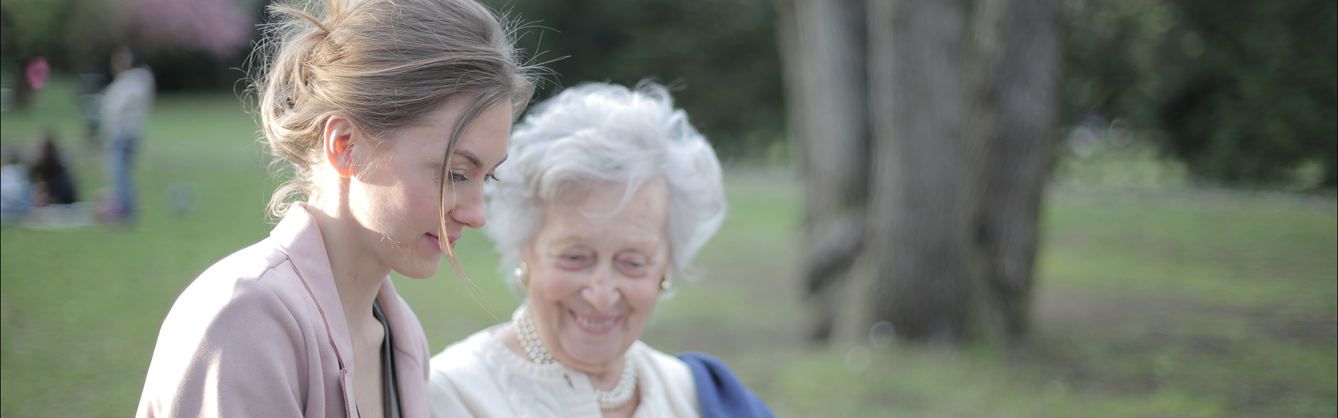 Free Stock photo of a teenage assisting an elderly woman on a bench in a park