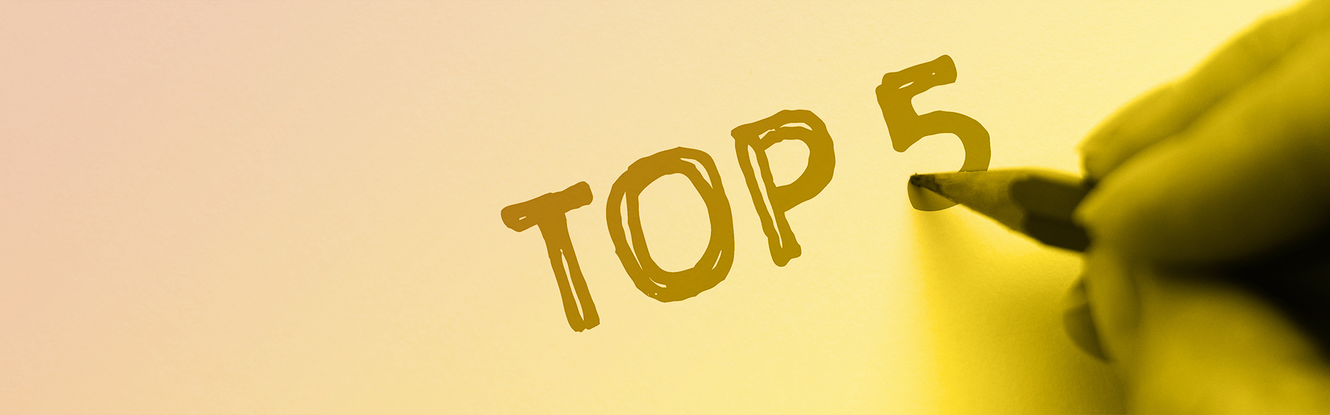 Stock photograph of fingers holding a pencil with the words top five written on a piece of paper