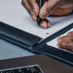 Stock photograph of a mans hands writing in a notebook