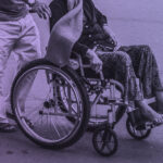 Cropped Stock photograph of a man pushing a person in a wheelchair on a tarmac road